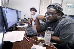 Photo of two Swan Leap employees sitting by a computer