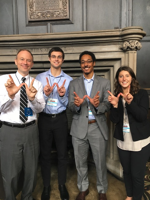 Jon Surdyk and Clinton challenge participants holding up the W symbol with their hands