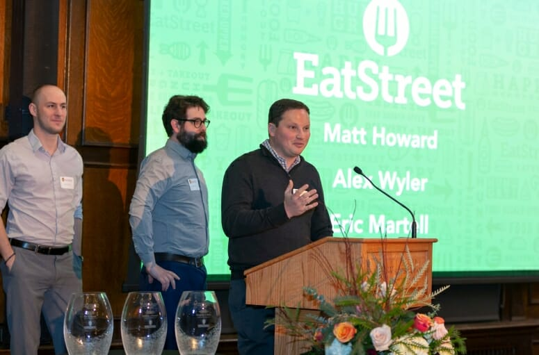 Eat Street founders Matt Howard, Alex Wyler, and Eric Martell stand at a podium next to a slide showing their names in the background, with award statues in the foreground