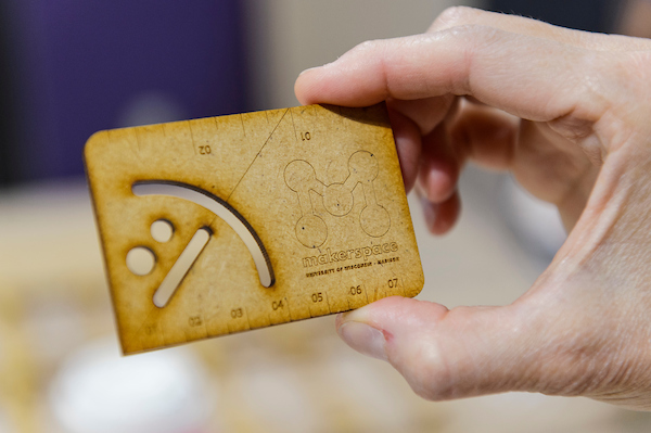 Person's hand holding a wooden business card with laser-cut graphics that say